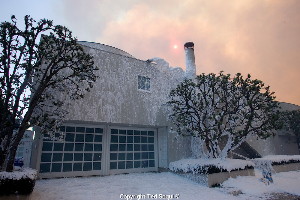 """The home of Jeffery Katzenberg on PCH. He has his own private fire fighting team spray white fire preventing foam on his home..Malibu wild fire..A brush fire that may have been sparked by downed power.lines swept across Malibu Canyon today, burning about 1,200 acres and destroying a church and several other structures in the beach-side community, including five homes..The fire was fed by high """"Santa Ana"""" type of winds which are very low in humidity and high in wind speed and dry out drought stricken vegetation..Wind speed were clocked at 60+ miles per hour."""