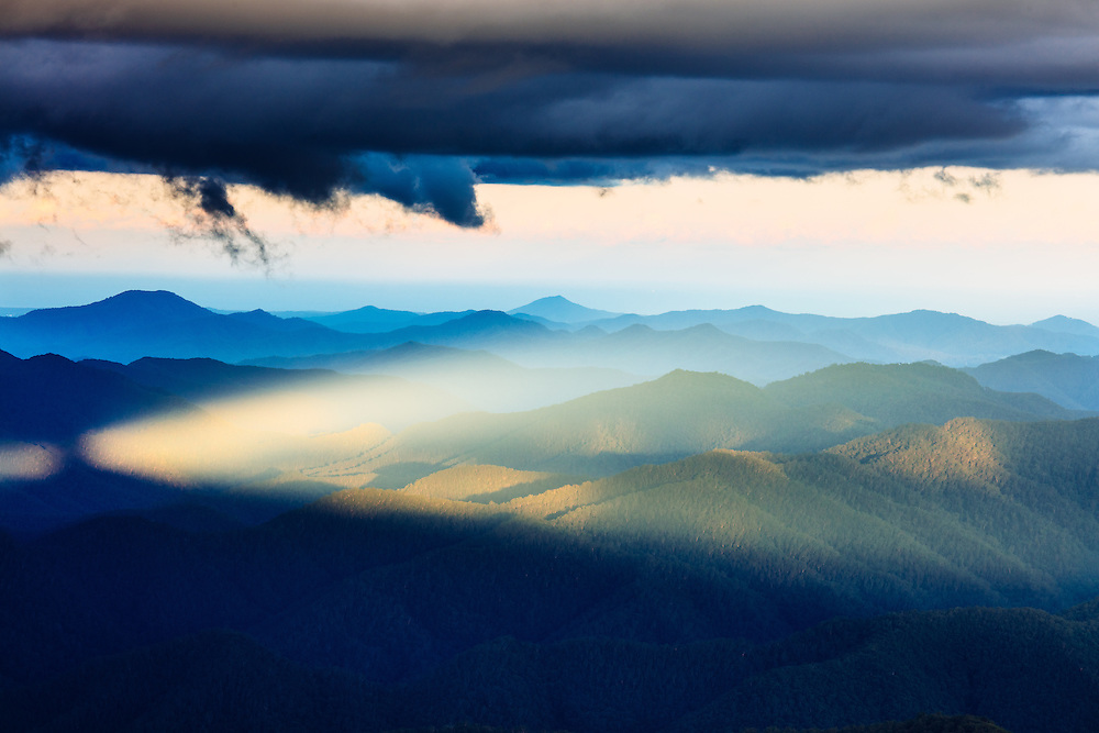 An unusual spear of light reaching through a gap in clouds forming a triangle shaped beam through the mountains. New England National Park.