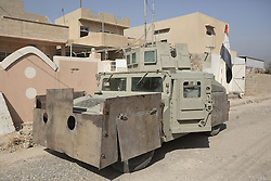 October 23, 2016 - Bartella, Nineveh, Iraq - A Humvee utility vehicle, modified with extra armour by its former Islamic State owners, is seen on a street whilst it waits repairs by the Iraqi Army in the recently liberated town of Bartella, Iraq...Bartella, a mainly Christian town with a population of around 30,000 people before being taken by the Islamic State in August 2014, was captured two days ago by the Iraqi Army's Counter Terrorism force as part of the ongoing offensive to retake Mosul. Although ISIS militants were pushed back a large amount of improvised explosive devices are still being found in the town's buildings. (Credit Image: © Matt Cetti-Roberts/London News Pictures via ZUMA Wire)