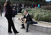 A man helps his wife with rolling up a ball of wool thread for knitting at the People's Park in Shanghai, China on 28 January 2009.