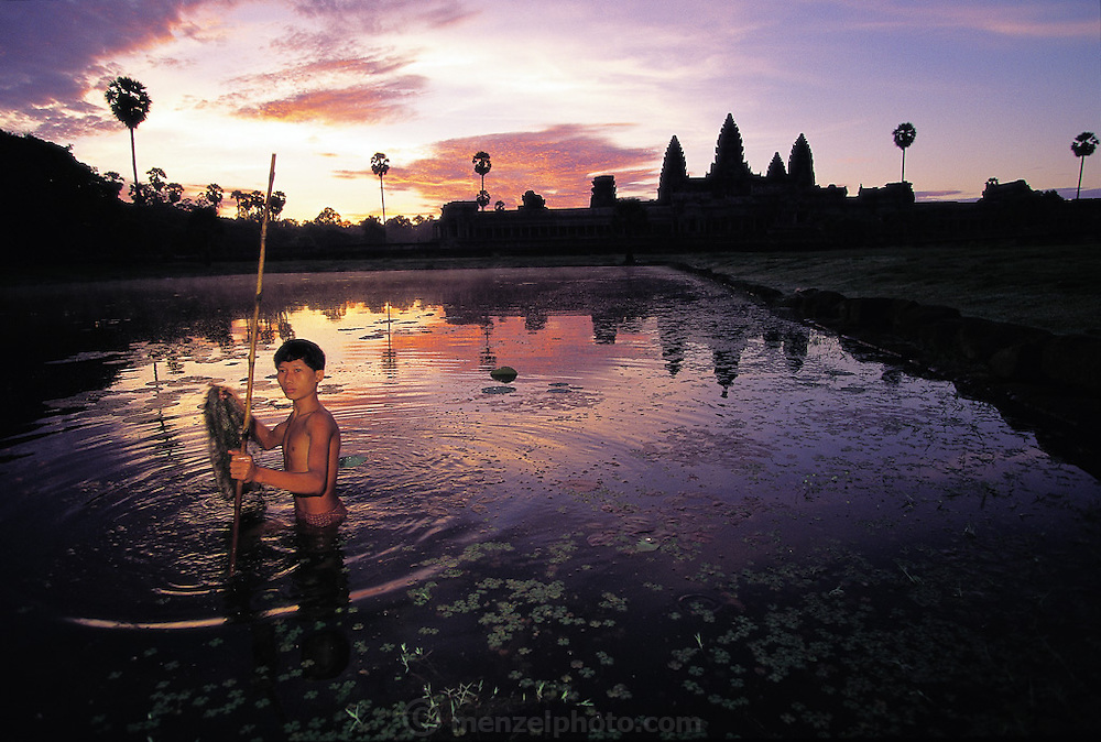 Dawn over the Angkor Wat ruins presents a background for a young Cambodian man's sunrise fishing chore, Angkor Wat, Cambodia. (Man Eating Bugs page 52,53)