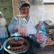 """TIMISOARA, ROMANIA - APRIL 21:  A woman prepares some """"mititei"""" (meat sausages) at her stall at the daily market on April 21, 2013 in Timisoara, Romania.  Romania has abandoned a target deadline of 2015 to switch to the single European currency and will now submit to the European Commission a programme on progress towards the adoption of the Euro, which for the first time will not have a target date. (Photo by Marco Secchi/Getty Images)"""