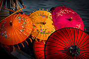 monks under parasols in canoe on Inle lake, Myanmar, Shan state