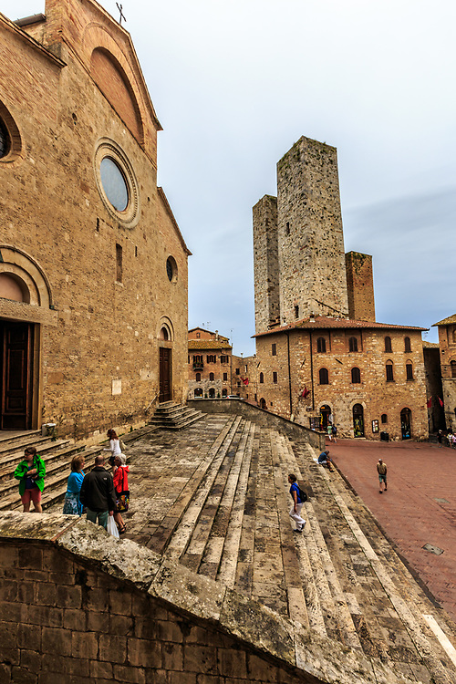 The Piazza del Duomo  in San Gimignano in Tuscany, Italy. This piazza is to the north of Piazza della Cistern and is connected by a passage adjacent to an open loggia. To the west, at the top of the square, stands the Collegiate Church, reached by a broad flight of steps.