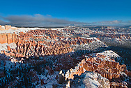 A snow covered Bryce Canyon greets the morning light, showing off the layered hoodoos.