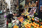 Italie, Napels, 7-3-2008..een van de karakteristieke nauwe straatjes in het centrum. Werknemer van een groentewinkel helpt een klant. De stad weet met zijn afval geen raad meer en in het hele gebied liggen illegale hopen afval. Een nieuwe vuilverbrandingsoven is pas in 2009 bedrijfsklaar. Tot die tijd heeft de maffia, camorra grote invloed op de afvalverwerking van deze stad...Industrieel afval en huishoudelijk afval veroorzaken grote water en bodemvervuiling, terwijl de streek een belangrijk tuinbouwgebied is...Foto: Flip Franssen