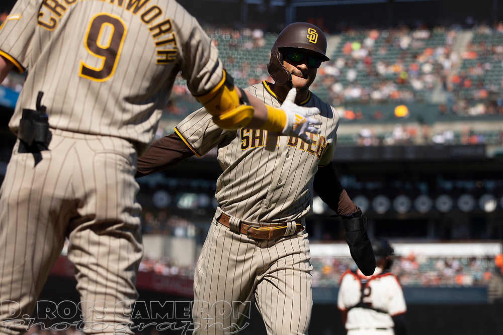 San Diego Padres' Trent Grisham, right, gets a congratulatory handshake from teammate Jake Cronenworth (9) after scoring on Manny Machado's single during the sixth inning of a baseball game against the San Francisco Giants, Saturday, Oct. 2, 2021, in San Francisco. (AP Photo/D. Ross Cameron)
