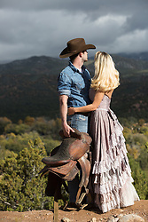 cowboy and a beautiful girl in a long antique dress looking at a mountain range