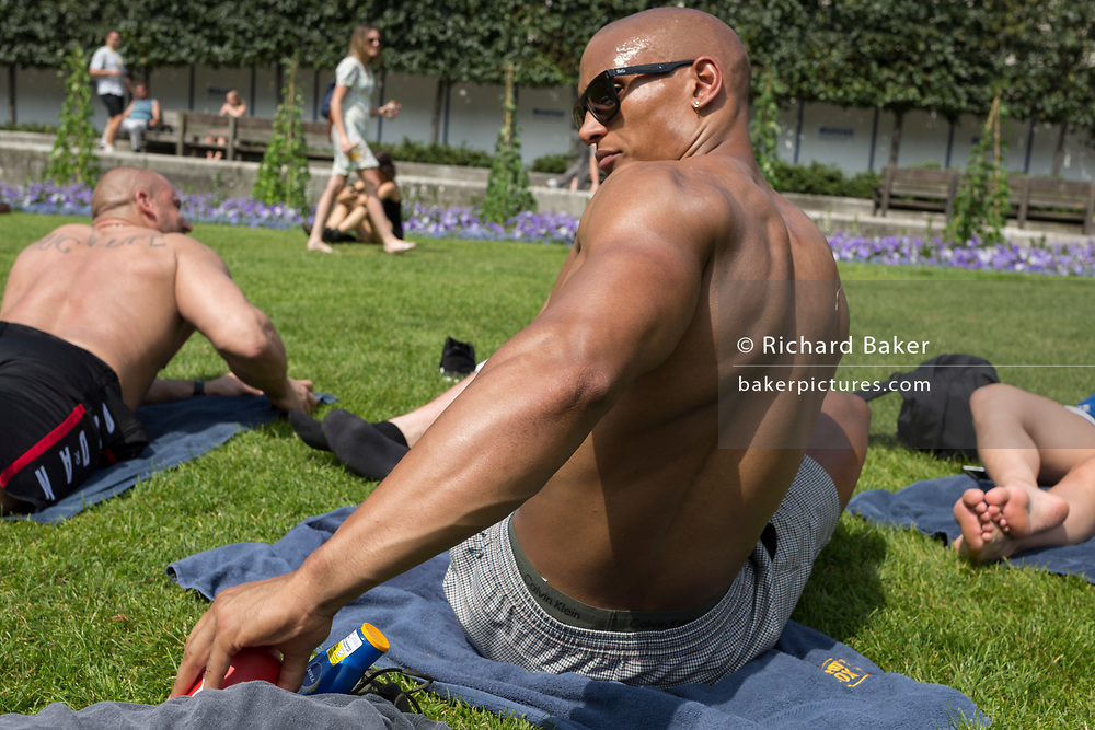 As heatwave temperatures climb to record levels - the hottest day of the year so far, office co-workers sunbathe on the grass beneath St. Paul's Cathedral in the City of London (the capital's financial district aka the Square Mile), on 25th July 2019, in London, England.