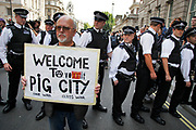 Man holds up a sign in protest which says: Welcome to Pig City, as police officers form lines to control protesters and in particular groups they suspect are part of anarchist organisations. An offshoot protest as part of the demonstration in Central London on a day of General Strike action by public sector workers and unions. Civil servants, teachers, health workers all came out on a day of peaceful march and protest against government cuts which look set to see their pensions change.