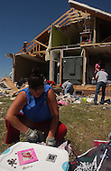"""Rainsville, Alabama: Melanie Sarratt organizes her daughter's photos and sorts change in front of her ruined house. At least seven houses in their subdivision--knicknamed """"Rainbow's End""""--where obliterated when one of many tornadoes swept through the area Wednesday. At least 32 people are confirmed dead in Dekalb County in northeastern Alabama. The Sarratt family survived. (PHOTO: MIGUEL JUAREZ LUGO)"""