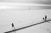 """On a wooden boardwalk that stretches across a sandy beach landscape, a young girl runs at full speed away from her mother and younger brother who walk along this walkway on the beach at Calais, France. It is low-tide, hazy winter sunshine makes soft shadows on the sand but there are few people out in the cold beyond except for a family in the surf approximately 200 yards away in the distance. Half-way back to the shore is a lone lifebelt attached to its pole in case of emergency. This near-deserted beach is an idyllic and tranquil place, allowing children to let off steam. Ffrom a personal documentary project entitled """"Next of Kin"""" about the photographer's two children's early years spent in parallel universes. Model released."""