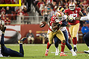 San Francisco 49ers running back Shaun Draughn (24) has the ball popped out of his hands by the Los Angeles Rams for a fumble at Levi's Stadium in Santa Clara, Calif., on September 12, 2016. (Stan Olszewski/Special to S.F. Examiner)