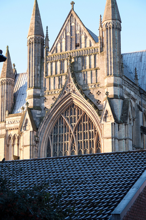 Early 13th century Early English east end of Beverley Minster with 9 light perpendicular east window of 1416 rises above the pantile rooftops.