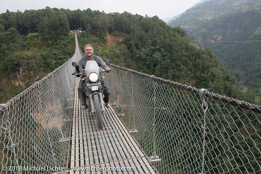 Kelly Modlin on the Kusma Gyadi Bridge, the tallest (443') and one of the longest (1,128') suspension bridges in the country, on Day-7 of our Himalayan Heroes adventure riding from Tatopani to Pokhara, Nepal. Monday, November 12, 2018. Photography ©2018 Michael Lichter.