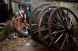 """A rickshaw puller washes in one of the community homes in Calcutta, INdia November 17, 2005. The hand rickshaw that was brought to Kolkata, formerly known under the British regime as Calcutta, India in 1900 by Chinese immigrants is being banned at the beginning of 2006. The city government want s to attract foreign investment and they say the hand-rickshaw """"wallahs"""" create an uncomfortable image of the city.  The pullers themselves do not have any ethical problems with pulling another man and justify their trade by saying thar rickshaws provide affordable transportation for the poor, do not pollute the environment and provide a desperately needed source of income.  The hand rickshaw is one of the oldest vehicles in the city and there are an estimated 18,000 rickshaw pullers who will be put out of work with no other possibilities. Most of the pullers live in the streets with their families or in a community shelter, a """"dera"""" with 20-25 other pullers. Most pullers make less than $2 per day but end up spending most of it on rent for the rickshaw, bribes to policemen and food. (Ami Vitale/Getty Images)"""