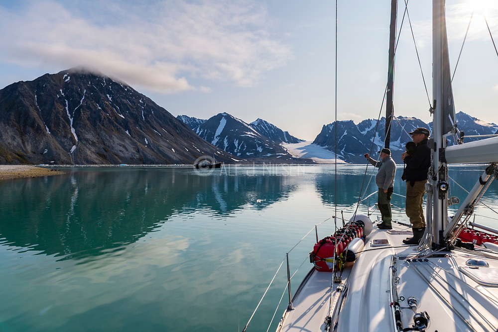 Sailboat and crew exploring madgalenefjorden, north-western Spitsbergen, Svalbard, Norway in August.