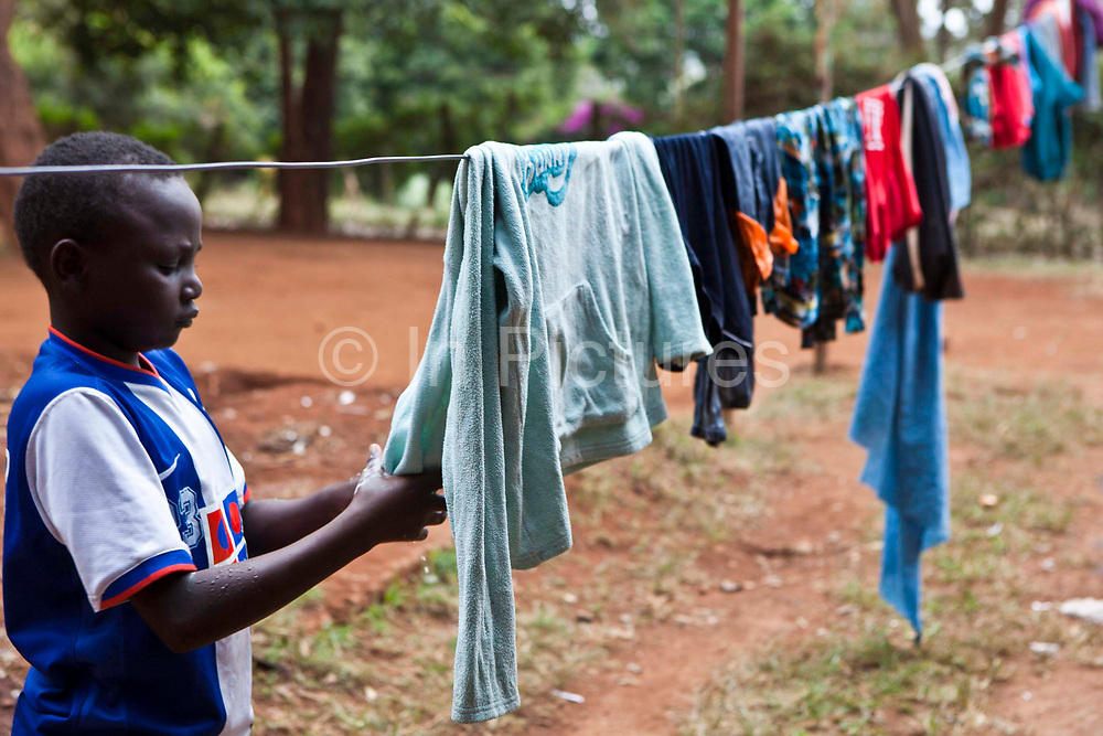 A young boy hangs out his washing at the AFCIC centre in Thika, Kenya. AFCIC - Action for children in conflict, help children who have been affected by various forms conflict or crisis.
