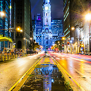 City Hall as seen from Broad Street after rain with traffic streaks. Reflection of City Hall in the puddle middle of frame.