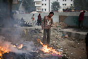 Homeless men gather round a fire at dawn near the banks of the Yamuna River in Delhi, India.