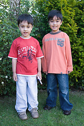 Portrait of two brothers in the garden smiling,