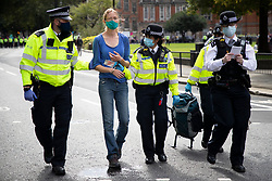 © Licensed to London News Pictures. 02/09/2020. London, UK. Police arrest an Extinction Rebellion protester after she glued herself to the a road outside the Houses of Parliament . The environmental activist group have continued to block roads around parliament in an attempt to disrupt PMQs.  Photo credit: George Cracknell Wright/LNP