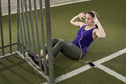 Young woman doing sit-ups and listening to music on football ground, Bavaria, Germany