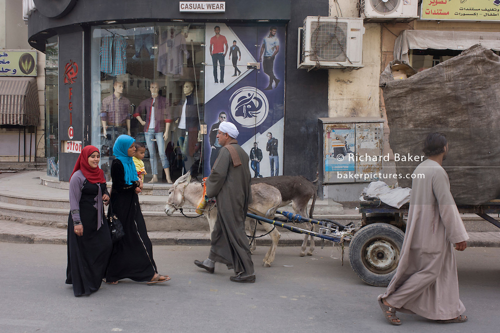 Egyptians pass a mens' clothing business displaying latest styles in modern Luxor, Nile Valley, Egypt.
