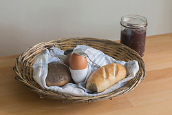 Baguette with buns and egg cup in a basket