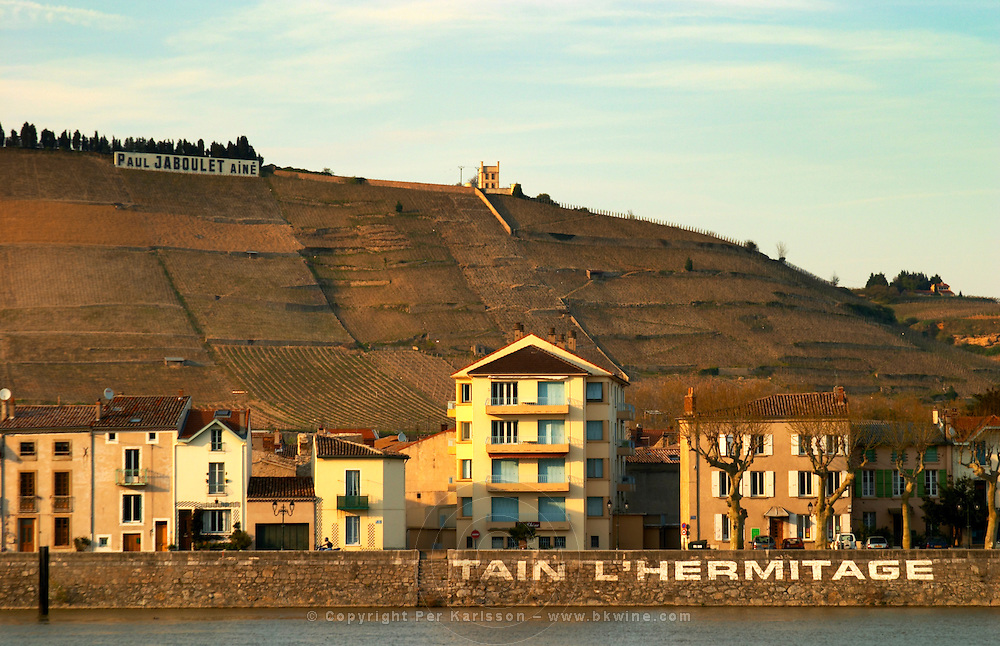 Along the river key side painted in large white letters Tain l'Hermitage. On top of the hill a sign Paul Jaboulet and the White House La Maison Blanche. The Hermitage vineyards on the hill behind the city Tain-l'Hermitage, on the steep sloping hill, stone terraced. Sometimes spelled Ermitage. Tain l'Hermitage, Drome, Drôme, France, Europe