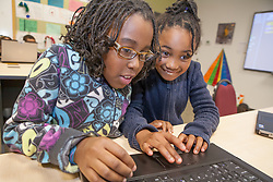 North America, United States, Seattle, after-school technology class, 2 girls working on laptop pc.  MR