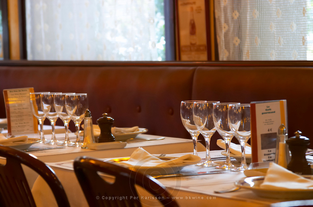 The classic restaurant brasserie Bolingrin with tables set with glasses and linen napkins and table cloth, knives and forks, salt shaker and pepper, Reims, Champagne, Marne, Ardennes, France, low light grainy grain
