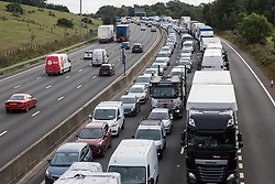 Traffic is queued on the M25 after climate activists from Insulate Britain block a slip road as part of a new campaign intended to push the UK government to make significant legislative change to start lowering emissions on 13th September 2021 in Godstone, United Kingdom. The activists, who wrote to Prime Minister Boris Johnson on 13th August, are demanding that the government immediately promises both to fully fund and ensure the insulation of all social housing in Britain by 2025 and to produce within four months a legally binding national plan to fully fund and ensure the full low-energy and low-carbon whole-house retrofit, with no externalised costs, of all homes in Britain by 2030 as part of a just transition to full decarbonisation of all parts of society and the economy.