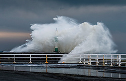© Licensed to London News Pictures. 13/12/2018. Aberystwyth, UK. Strong gale force winds and a high tide combine to hammer huge waves against the sea defences in Aberystwyth on the Cardigan Bay coast of west Wales. A bitterly cold easterly wind is blowing with gusts reaching 36mph, and a frost is forecast overnight as the skies clear. Photo credit: Keith Morris/LNP
