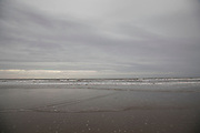 The beach and sea at seaside town of Borth on a grey gloomy day in Wales, United Kingdom.