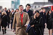 Commuters walk across London bridge to get to work in the city of London. Thousands of commuters arrive into London Bridge station everyday and walk to work.