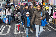 """Families out shopping on Pettycoat Lane Market in the City of London, UK. Petticoat Lane Market is a fashion and clothing market in the East End of London. It consists of two adjacent street markets. Wentworth Street Market is open six days a week, and Middlesex Street Market is open on Sunday only. The name Petticoat Lane came from not only the sale of petticoats but from the fable that """"they would steal your petticoat at one end of the market and sell it back to you at the other."""""""