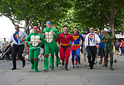 Stag party friends dressed up in superhero costumes start their stag do running along the Southbank in London, UK. This is a right of passage style gathering where the objective is to have fun, be a little silly, and drink a considerable amount of alcohol.