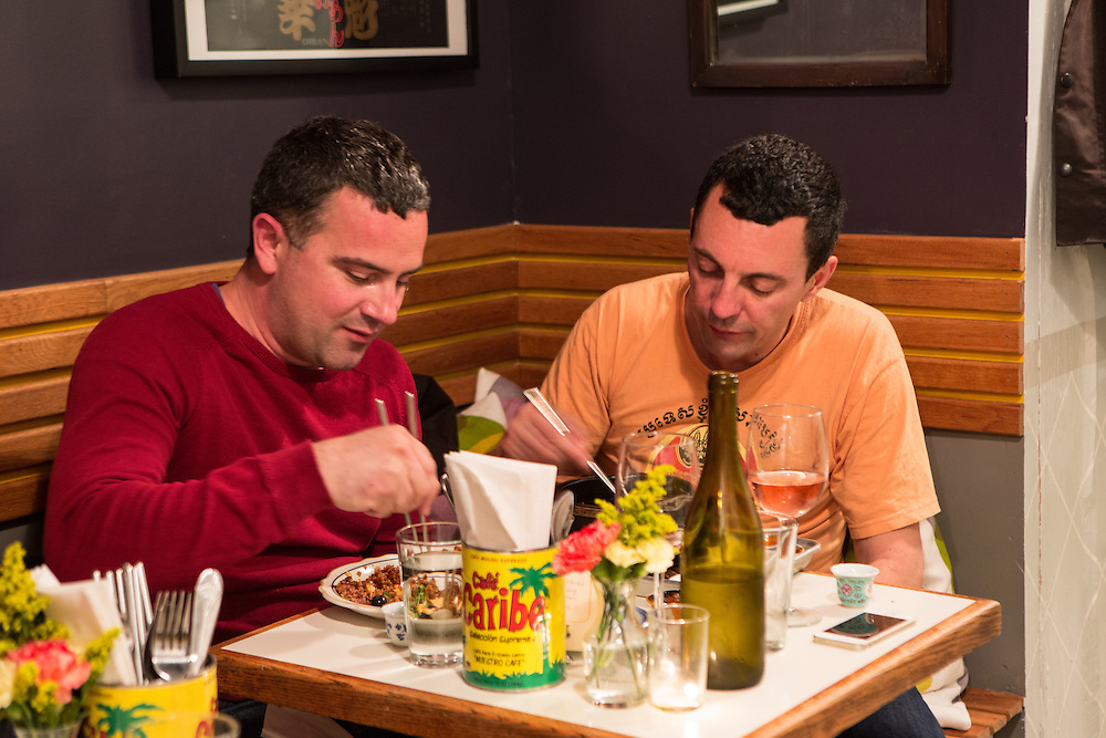 Brooklyn, NY - 26 April 2014.  Two men are eating at a small table in a rear nook at Dotory.