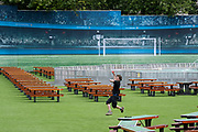 Surrounded by empty tables, a member of staff bowls a ball inside the Fan Zone, the enclosed area in Trafalgar Square for public-balloted ticket-holders during the Euro football tournament, on 8th July 2021, in London, England.