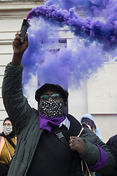 London, UK. 1st May, 2021. A man holds a purple smoke grenade in Trafalgar Square at a Kill The Bill demonstration as part of a National Day of Action to coincide with International Workers Day. Nationwide protests have been organised against the Police, Crime, Sentencing and Courts Bill 2021, which would grant the police a range of new discretionary powers to shut down protests.