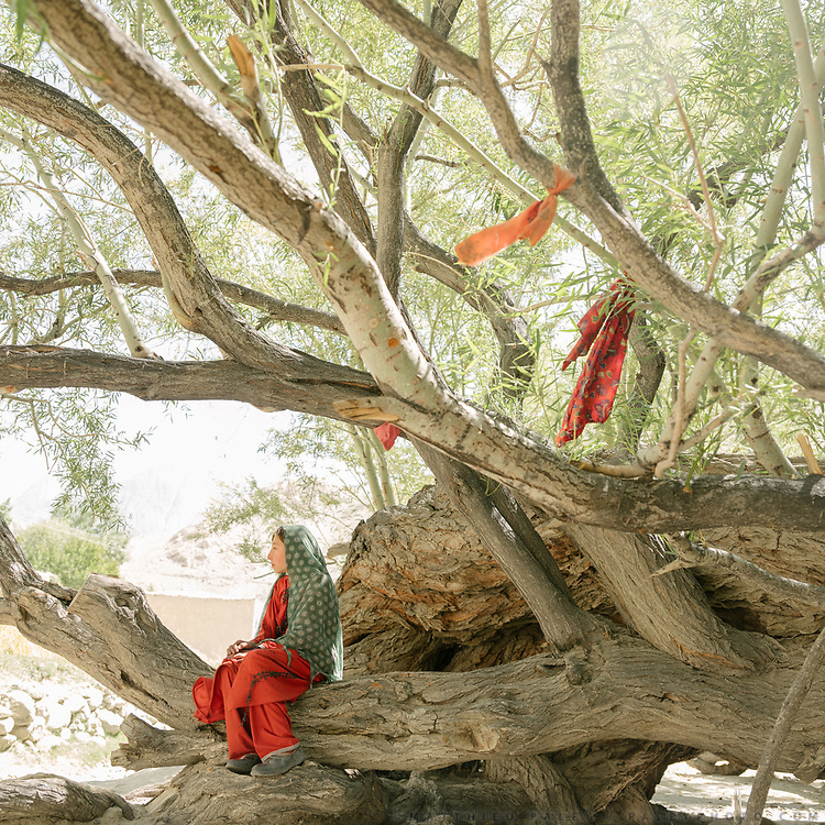 """Teenage girl sits below a tree. Cloth attached on tree, for good luck, at the pre-islamic shrine named """"Saïd Brom"""".  The traditional life of the Wakhi people, in the Wakhan corridor, amongst the Pamir mountains."""