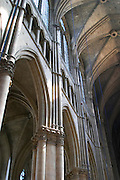 The Reims cathedral with its high gothic arched vaults and sun shining through the stained glass windows, Reims, Champagne, Marne, Ardennes, France, low light grainy grain