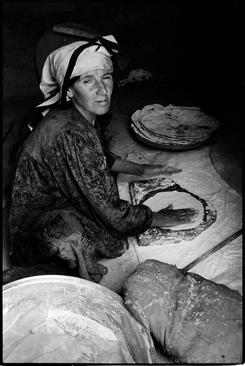 A Kurdish woman makes bread at the camp for internally displaced people (IDP) at at the Benaslawa Tent Camp. Despite some basic U.N. help, the camp is squalid and poor, with sewage in the streets, no work, and few comforts.