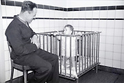 father watching baby in the box indoors 1960s