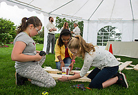 """Kaylee Richard, Sadie Fortune and Violet Brier work together building a picnic table during the Winnipesaukee Wine Festival Thursday evening.  Proceeds raised from the evening will go to the """"Girls At Work"""" organization.   (Karen Bobotas/for the Laconia Daily Sun)"""