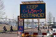 Nederland, Nijmegen, 15-4-2020  Een elektronisch mededelingenbord herinnert de mensen eraan voldoende afstand te houden, houd 1.5. meter afstand op de waalkade .Foto: Flip Franssen
