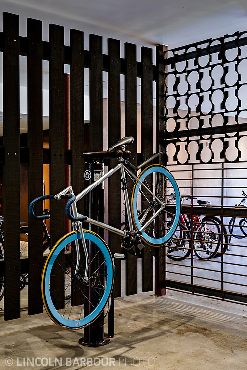 University House student housing apartment in Eugene, OR. Designed by Mahlum Architects. A fixed gear bike with blue deep v rims in a work stand.