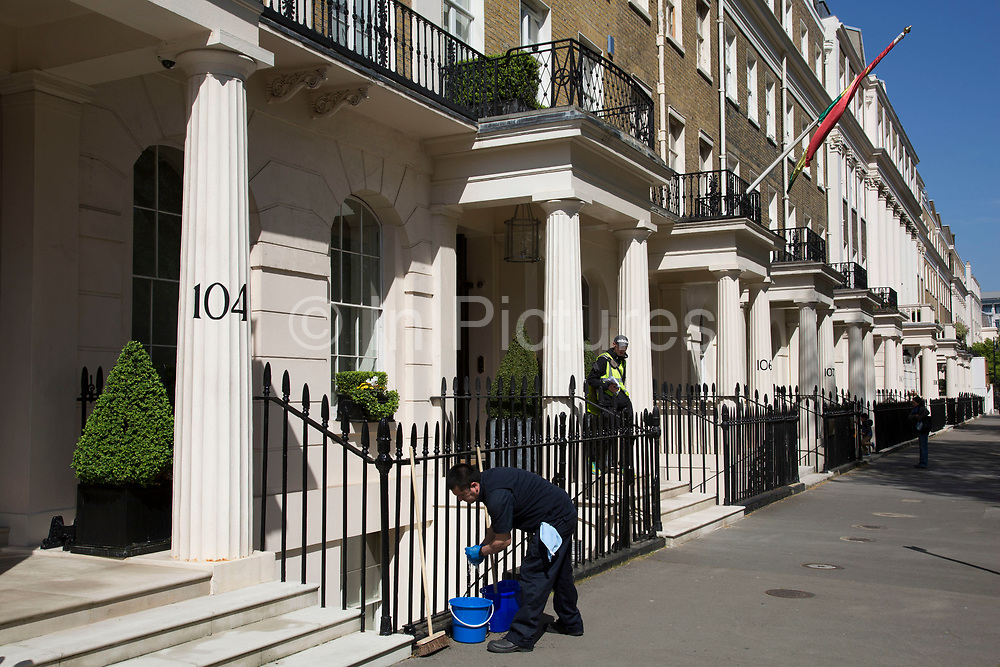 Cleaner washing fences on Eaton Square in Belgravia. In a selected few boroughs of West London, wealth has changed over the last couple of decades. Traditionally wealthy parts of town, have developed into new affluent playgrounds of the super rich. With influxes of foreign money in particular from the Middle-East. The UK capital is home to more multimillionaires than any other city in the world according to recent figures. Boasting a staggering 4,224 'ultra-high net worth' residents - people with a net worth of more than $30million, or £19.2million.. London, England, UK.