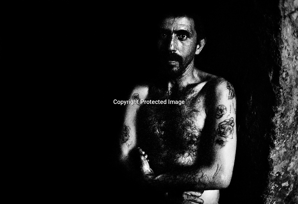 Bonifac (35), unemployed. No education. He has names of former girlfriends tattooed on his arms.